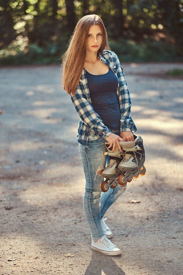 Retrato de una muchacha hermosa con la camisa y los vaqueros, rodillos del paño grueso y suave del pelo que lleva largo de los co imagen de archivo libre de regalías