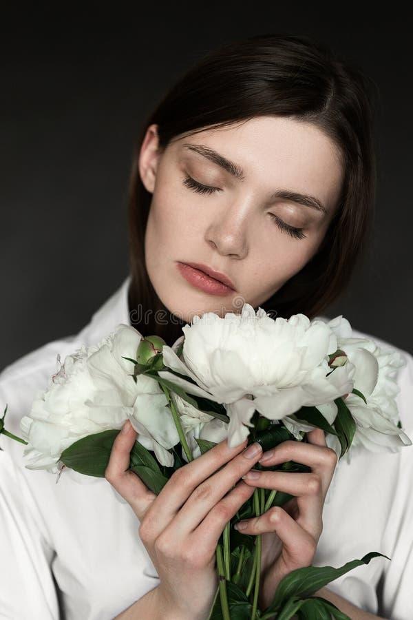Retrato de una muchacha hermosa con las peonías Foto que retoca de la belleza Moda y concepto del cosmético fondo gris del estudi imagen de archivo libre de regalías