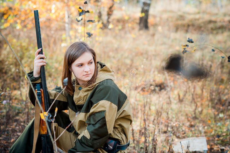 Retrato de una muchacha hermosa en cazador del camuflaje con la escopeta foto de archivo libre de regalías