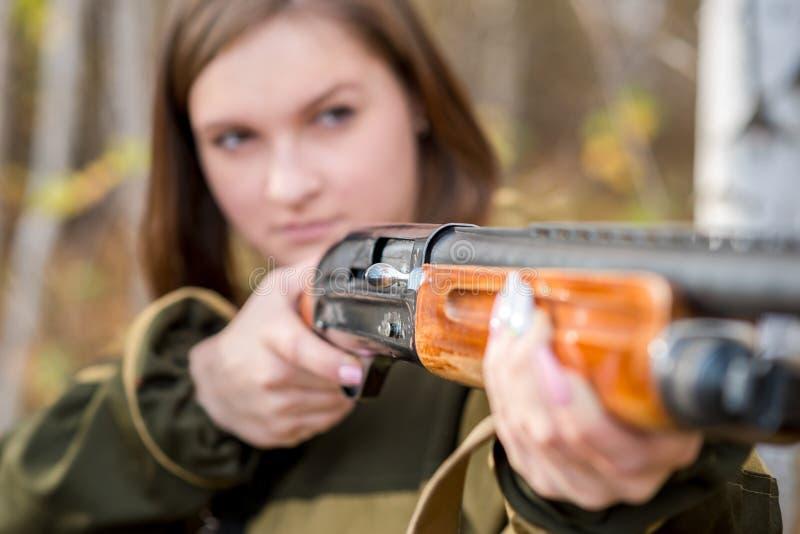 Retrato de una muchacha hermosa en cazador del camuflaje con la escopeta fotografía de archivo