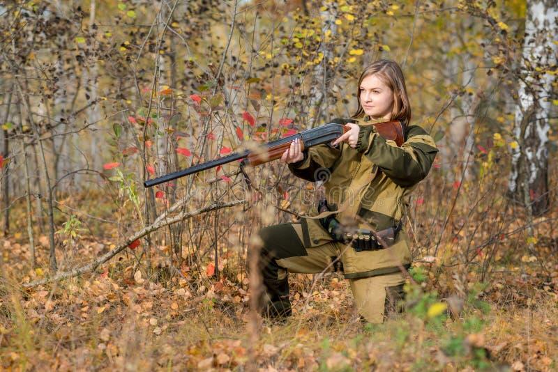 Retrato de una muchacha hermosa en cazador del camuflaje con la escopeta imágenes de archivo libres de regalías