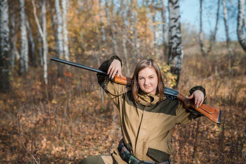 Retrato de una muchacha hermosa en cazador del camuflaje con la escopeta fotos de archivo libres de regalías