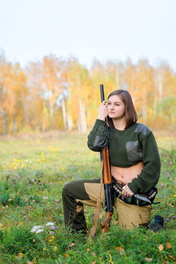 Retrato de una muchacha hermosa en cazador del camuflaje con la escopeta fotos de archivo