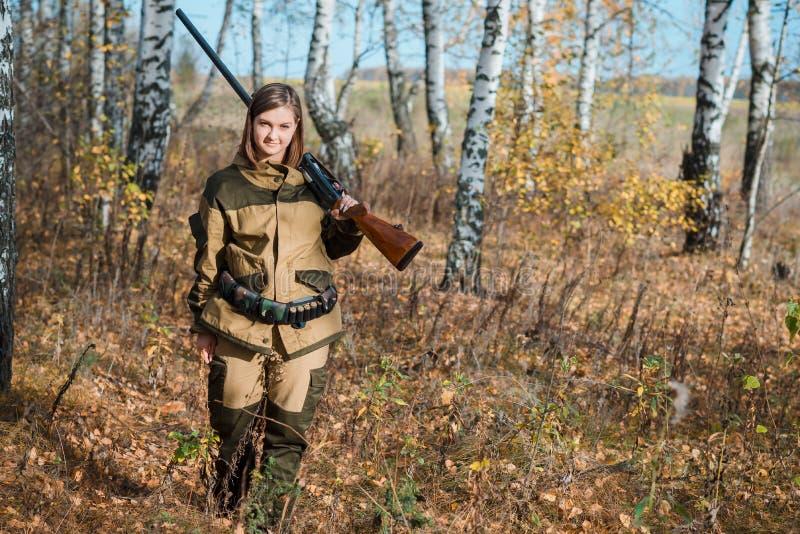 Retrato de una muchacha hermosa en cazador del camuflaje con la escopeta imagenes de archivo