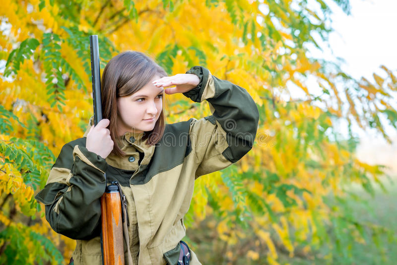 Retrato de una muchacha hermosa en cazador del camuflaje con la escopeta imagen de archivo