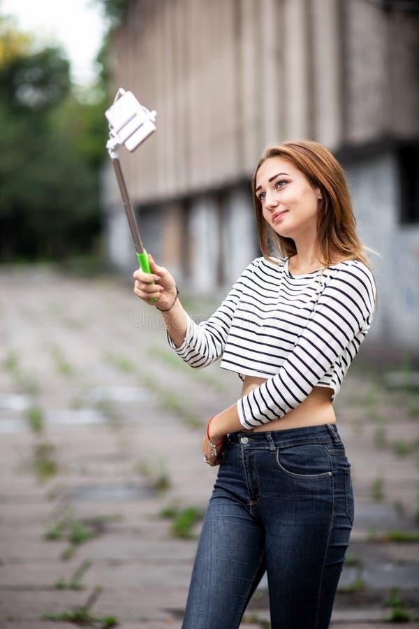 Retrato de una muchacha hermosa en una ciudad que presenta al smartphone en el palillo del selfie, mujer joven que hace el selfie fotografía de archivo