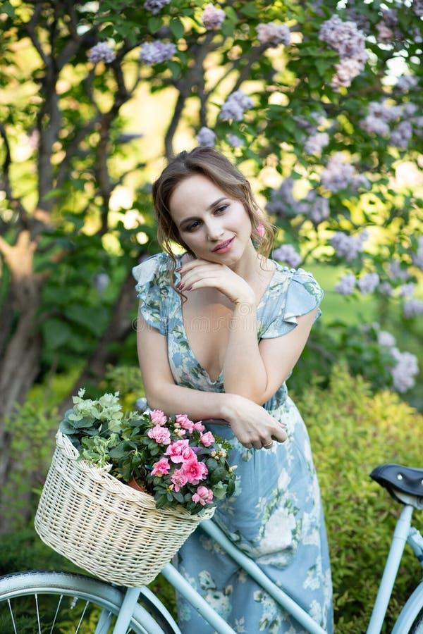 Retrato de una muchacha hermosa en el bosque, sosteniendo una bici con una cesta de flores, detr?s de los rayos del sol, un azul  imagen de archivo