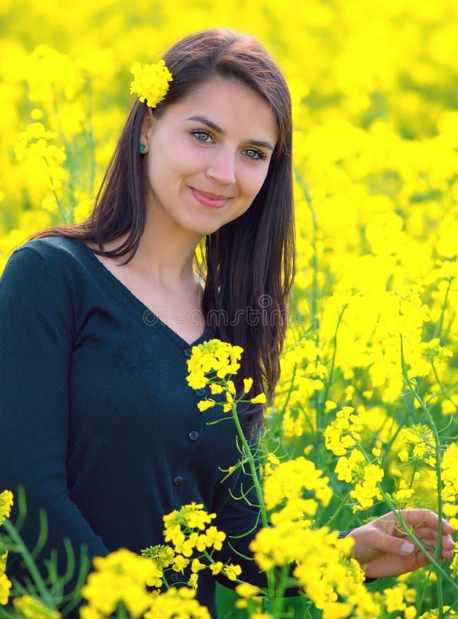 Retrato de una muchacha hermosa en el campo de la colza imagen de archivo