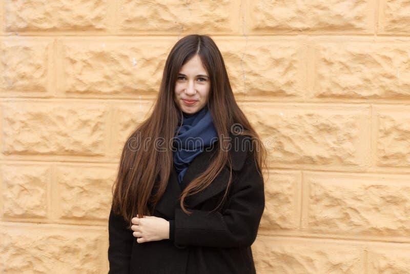 Retrato de una muchacha hermosa en el fondo de una pared anaranjada fotografía de archivo libre de regalías