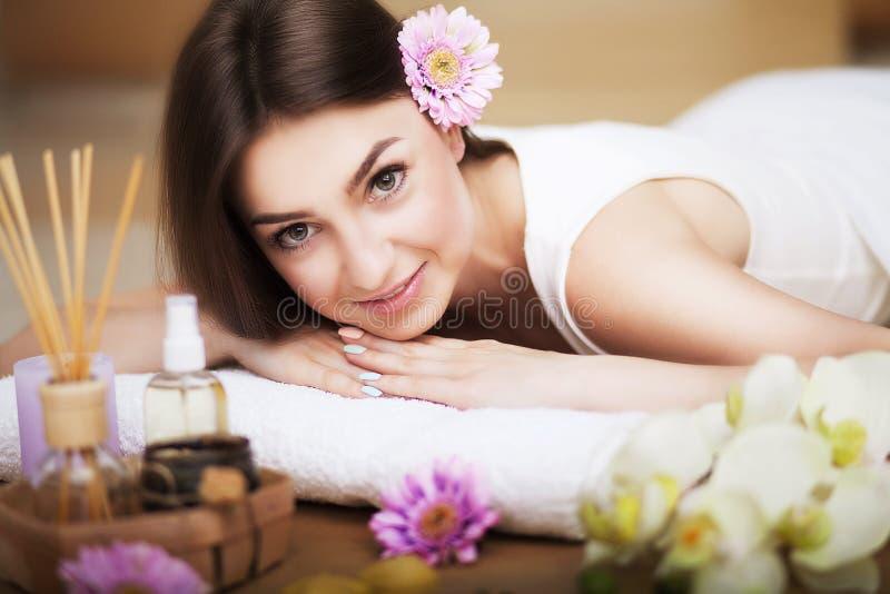 Retrato de una muchacha hermosa en un balneario Trate la mirada con suavidad Flores en pelo Aceite del aroma Gabinete del masaje  fotos de archivo