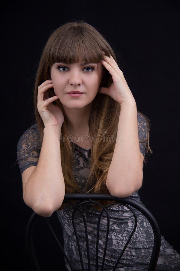 Retrato de una muchacha hermosa en un fondo negro foto de archivo libre de regalías