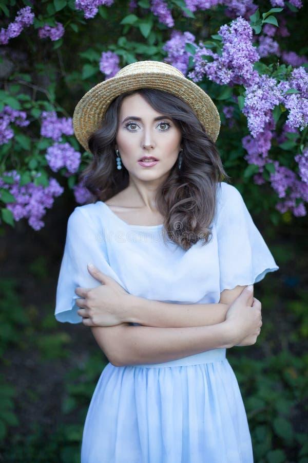 Retrato de una muchacha hermosa en un jardín de la lila Una mujer camina en un parque florecido Vacaciones de verano en el jardín foto de archivo libre de regalías