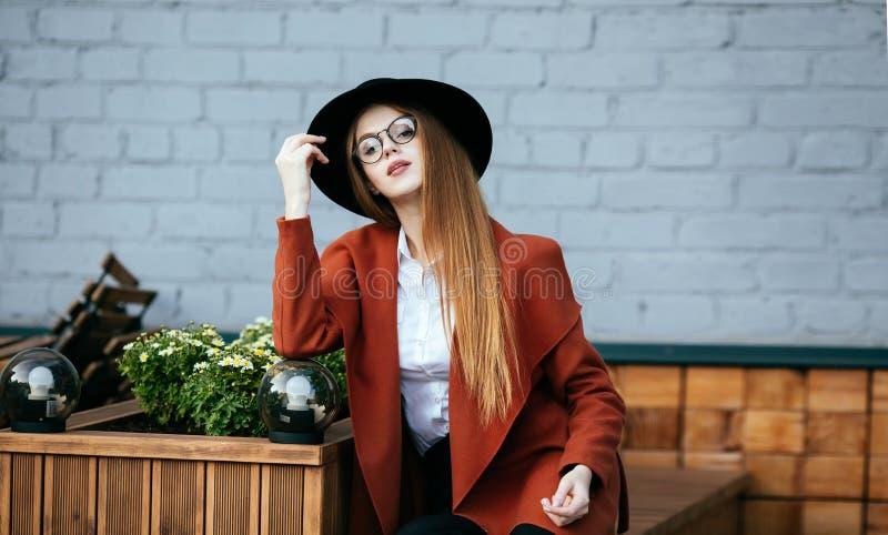 Retrato de una muchacha hermosa en un sombrero y una capa imagen de archivo libre de regalías