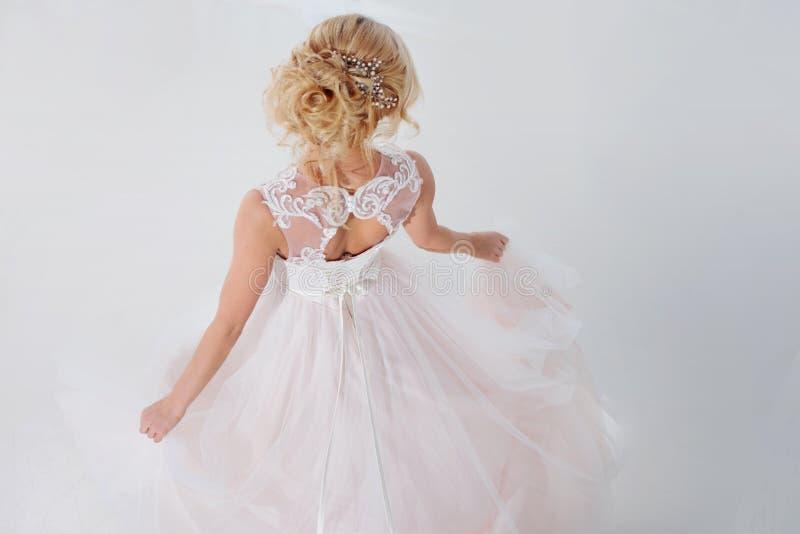 Retrato de una muchacha hermosa en un vestido de boda Novia del baile, fondo blanco Visión superior back fotos de archivo