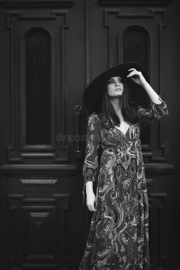 Retrato de una muchacha hermosa en un vestido con un sombrero en la puerta imagen de archivo libre de regalías