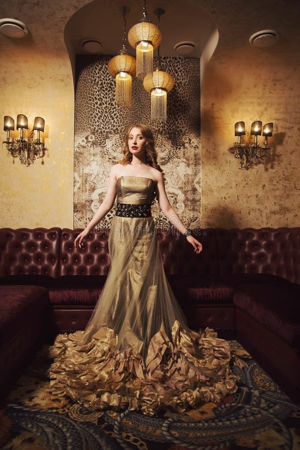 Retrato de una muchacha hermosa en un vestido del oro en interior hermoso foto de archivo libre de regalías
