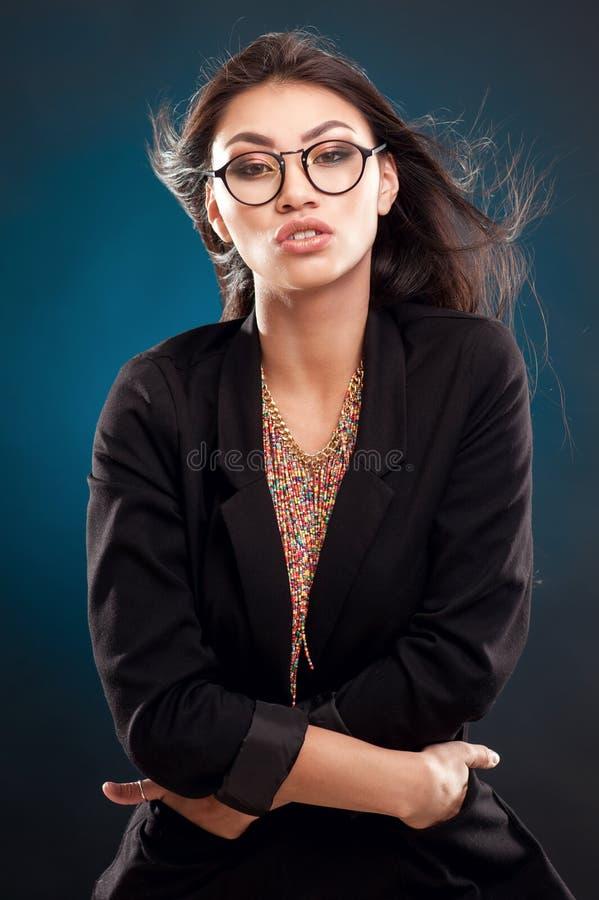 Retrato de una muchacha hermosa en vidrios redondos en un fondo azul en el estudio fotos de archivo