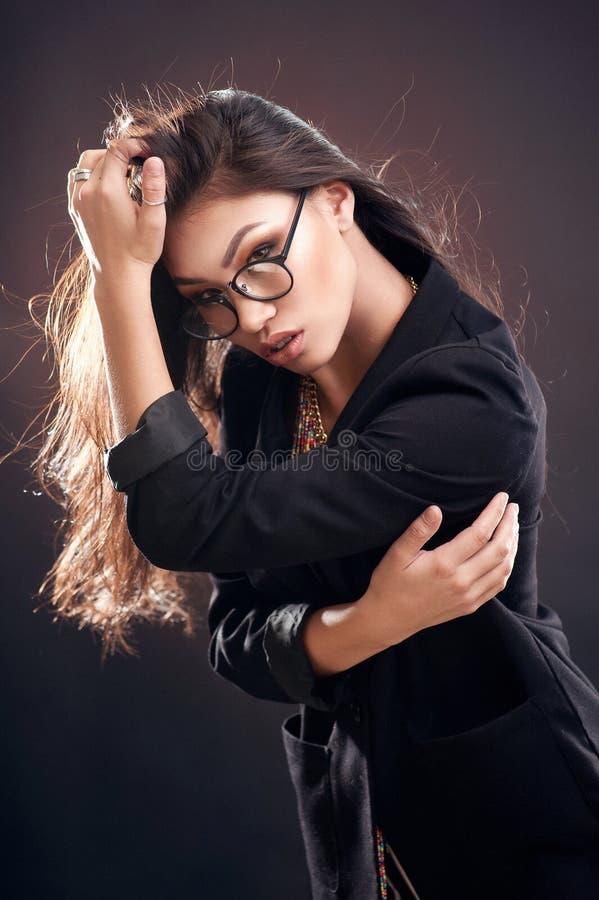 Retrato de una muchacha hermosa en vidrios redondos en un fondo marrón en el estudio fotografía de archivo
