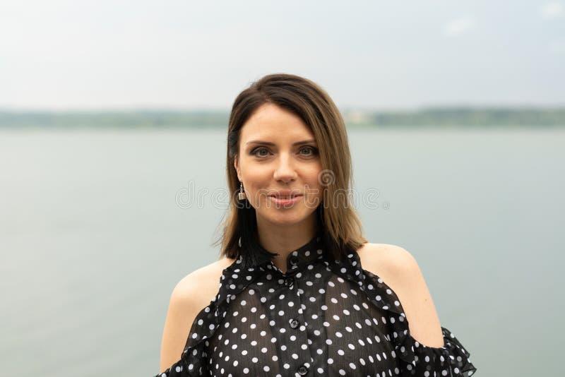 Retrato de una muchacha hermosa joven cerca del lago fotografía de archivo
