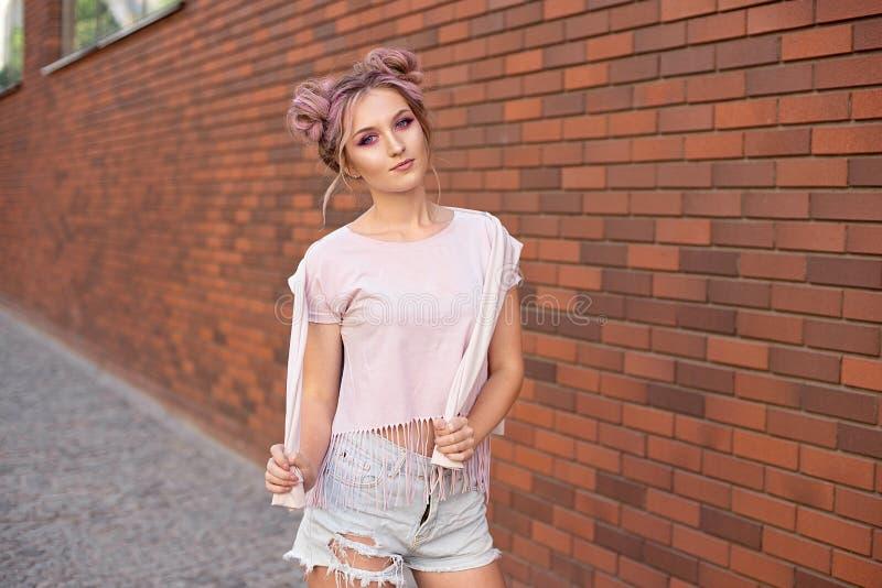 Retrato de una muchacha hermosa joven con el bollo rosado del pelo que sonríe contra una pared de ladrillo roja fotografía de archivo