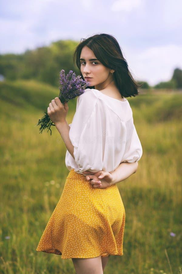 Retrato de una muchacha hermosa joven con un ramo de lavanda imagen de archivo libre de regalías