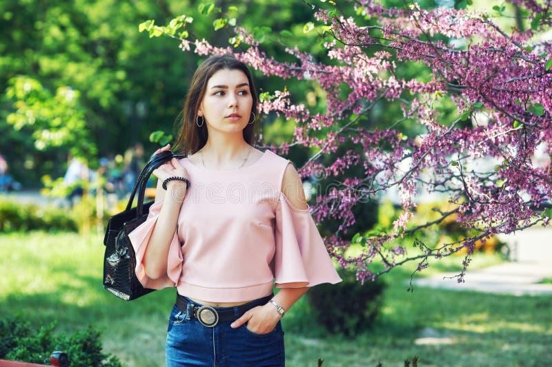 Retrato de una muchacha hermosa joven que plantea el modelo en las calles de una ciudad europea, en un fondo de árboles florecien fotos de archivo