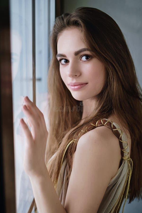 Retrato de una muchacha hermosa joven que se coloca cerca de una ventana imagenes de archivo