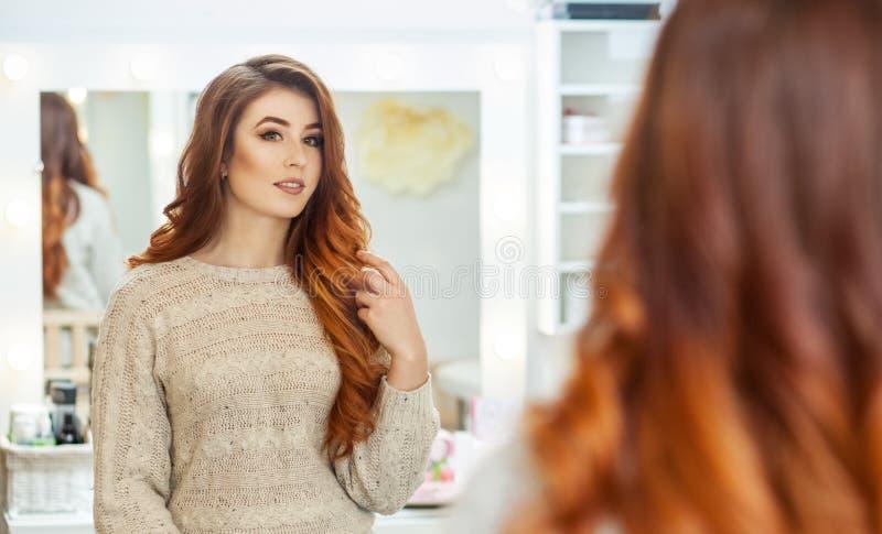 Retrato de una muchacha hermosa, pelirroja con el pelo largo en un salón de belleza fotografía de archivo