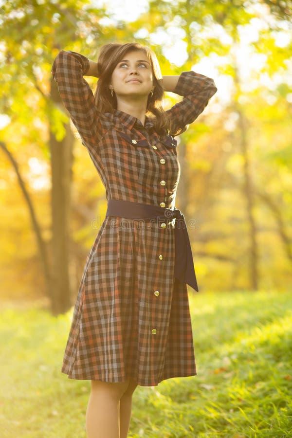 Retrato de una muchacha hermosa que camina en la naturaleza en el otoño, mujer joven que disfruta de la situación de la sol en un foto de archivo