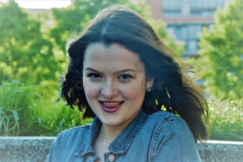 Retrato de una muchacha joven, atractiva, que pone hacia fuera su lengua suavemente imagenes de archivo