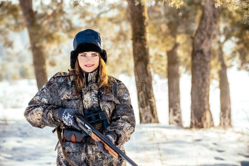 Retrato de una muchacha joven hermosa del cazador en un bosque del invierno, con referencia a fotos de archivo