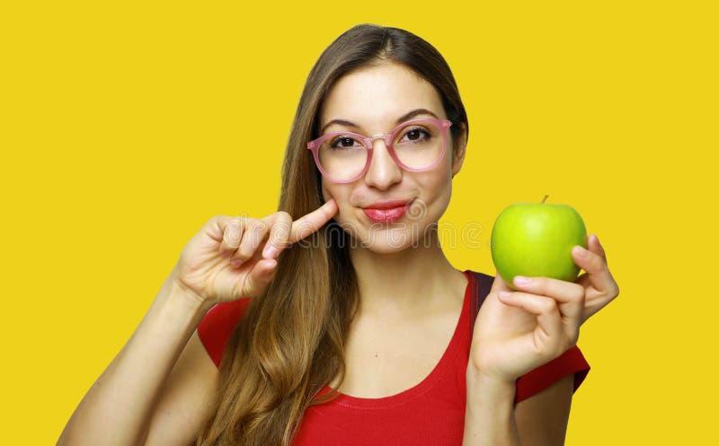 Retrato de una muchacha joven sonriente del empollón de la escuela que sostiene una manzana que gesticula como la buena comida sa fotografía de archivo libre de regalías