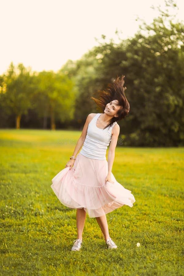Retrato de una muchacha linda hermosa en una falda morena romántica con adentro un jardín verde que presenta y que sonríe foto de archivo libre de regalías