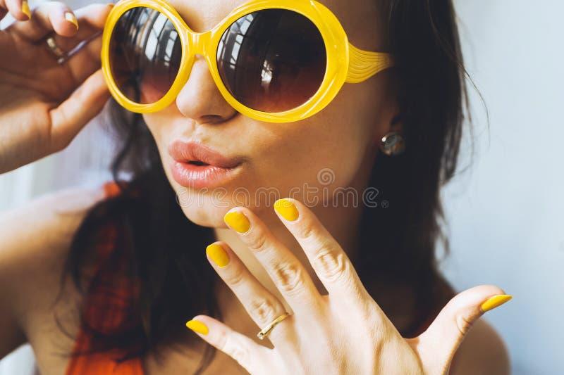 Retrato de una muchacha morena atractiva joven hermosa con los ojos expresivos y labios llenos, y gafas de sol que presentan para fotos de archivo libres de regalías
