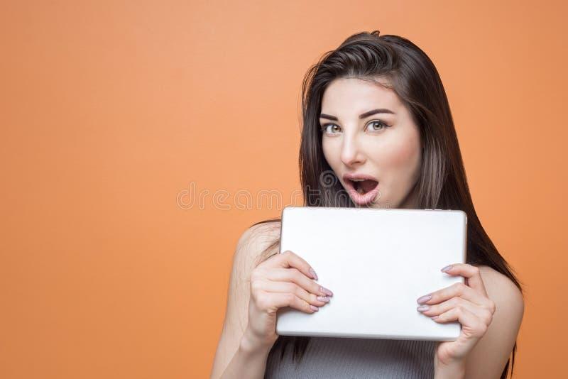 Retrato de una muchacha morena emocionada joven con la tableta en sus manos que miran la cámara con la boca abierta contra fondo  imágenes de archivo libres de regalías