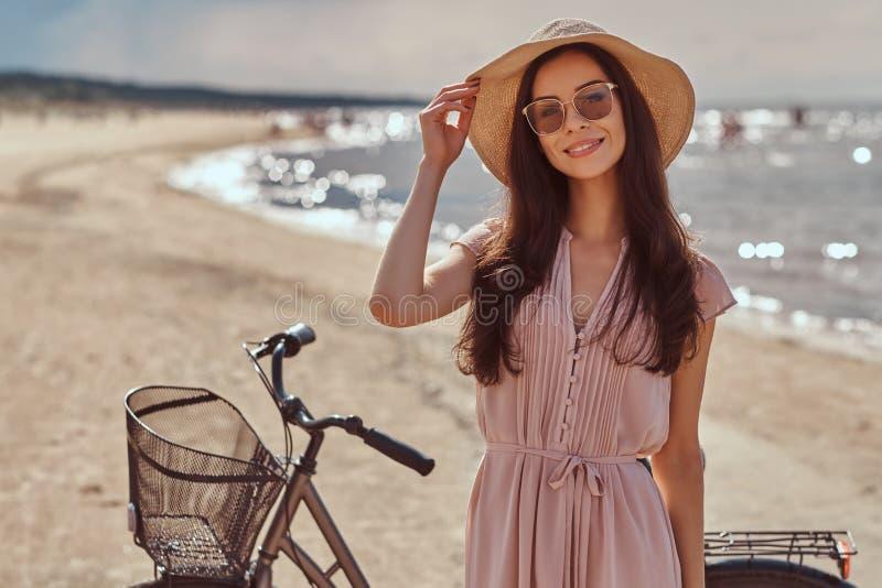Retrato de una muchacha morena hermosa sonriente con el pelo largo en las gafas de sol y las gafas de sol que llevan un vestido e imagen de archivo libre de regalías