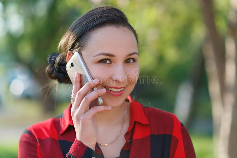 Retrato de una muchacha morena joven feliz con un smartphone en su mano, aumentado a su oído Muchacha que habla en móvil y la son foto de archivo libre de regalías