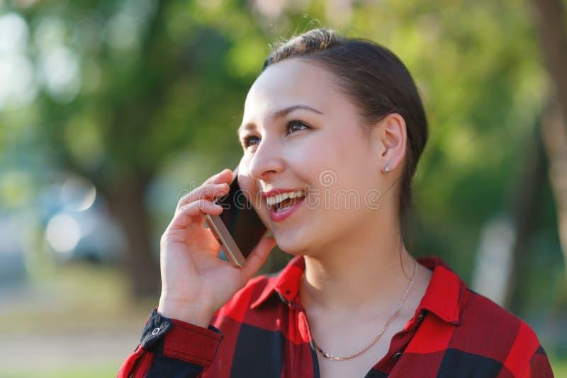 Retrato de una muchacha morena joven feliz con un smartphone en su mano, aumentado a su o?do Muchacha que habla en m?vil y la son fotografía de archivo libre de regalías