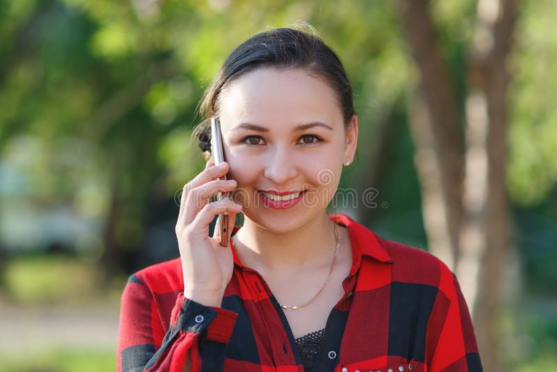 Retrato de una muchacha morena joven feliz con un smartphone en su mano, aumentado a su o?do Muchacha que habla en m?vil y la son fotografía de archivo