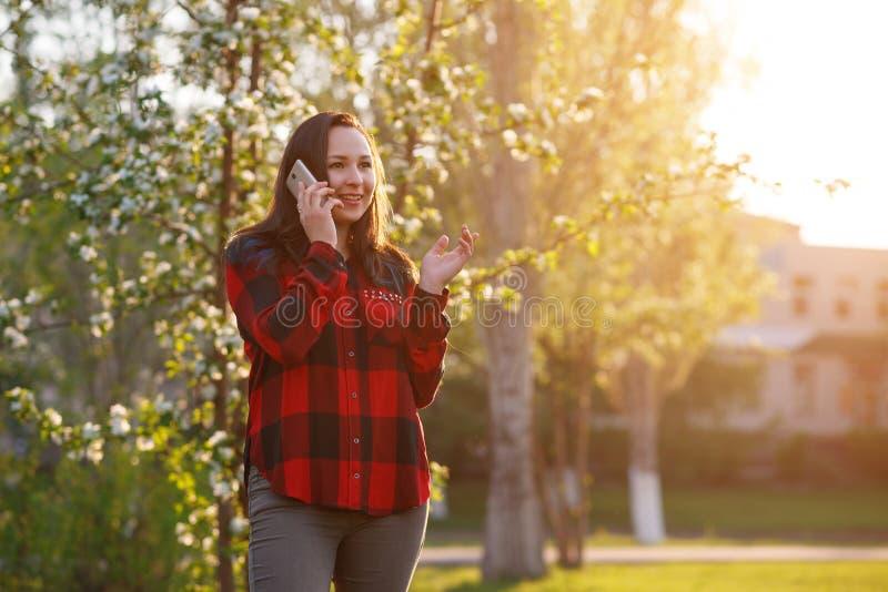 Retrato de una muchacha morena joven feliz con un smartphone en su mano, aumentado a su o?do Muchacha que habla en m?vil y la son imagen de archivo