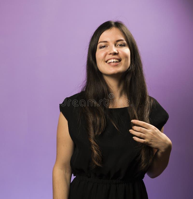 Retrato de una muchacha morena sonriente encantadora en un fondo púrpura foto de archivo