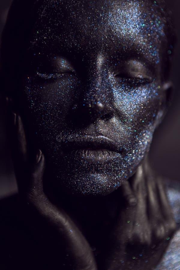 Retrato de una muchacha negra con los ojos grandes pintados con la pintura imagen de archivo