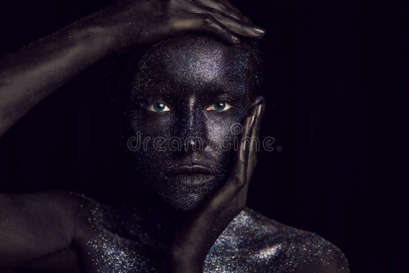 Retrato de una muchacha negra con los ojos grandes pintados con la pintura fotografía de archivo