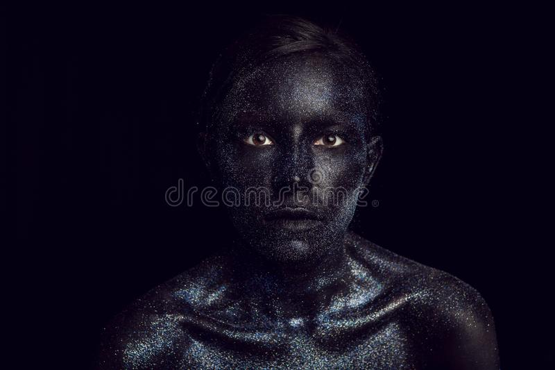 Retrato de una muchacha negra con los ojos grandes pintados con la pintura fotos de archivo