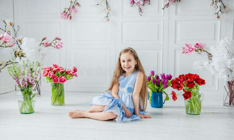 Retrato de una muchacha de ojos azules hermosa, niña entre las flores de la primavera en un cuarto brillante imagen de archivo