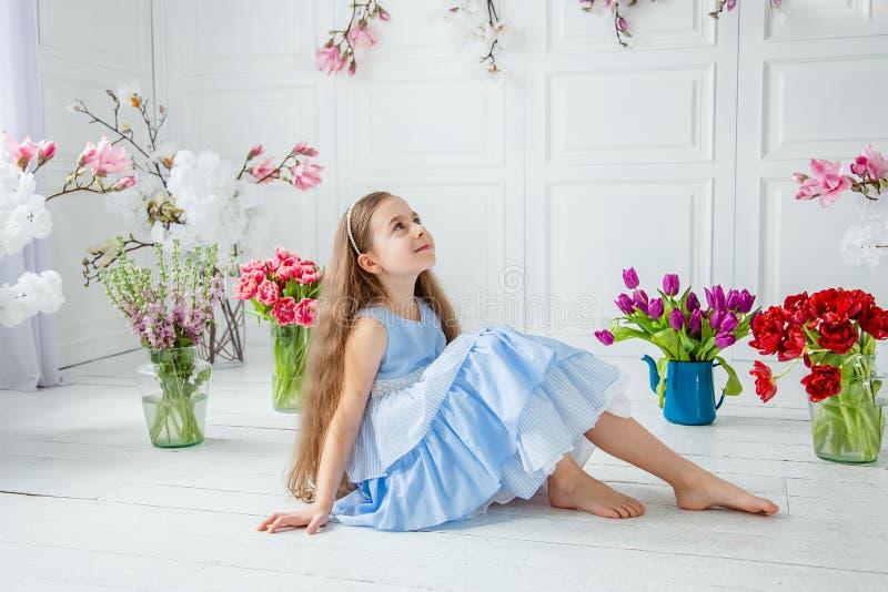 Retrato de una muchacha de ojos azules hermosa, niña entre las flores de la primavera en un cuarto brillante fotografía de archivo