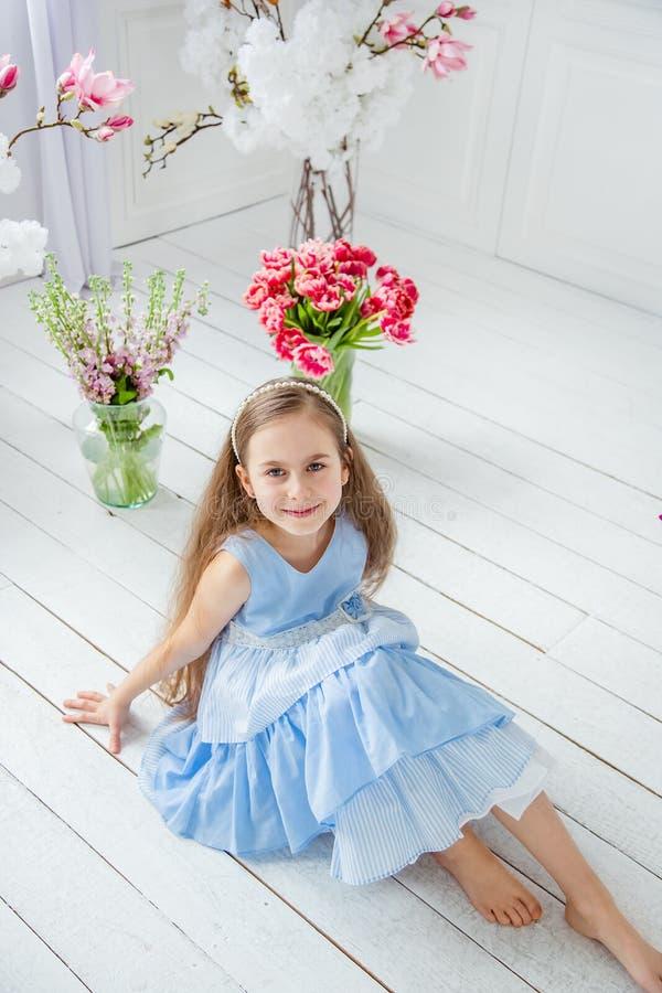 Retrato de una muchacha de ojos azules hermosa, niña entre las flores de la primavera en un cuarto brillante fotos de archivo