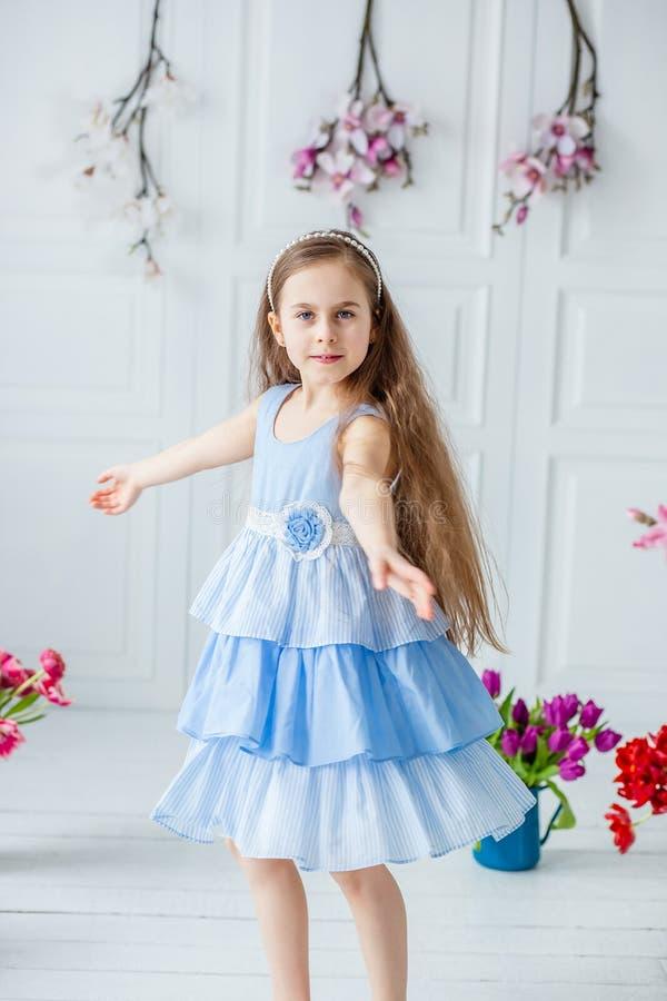 Retrato de una muchacha de ojos azules hermosa, niña entre las flores de la primavera en un cuarto brillante imagen de archivo libre de regalías