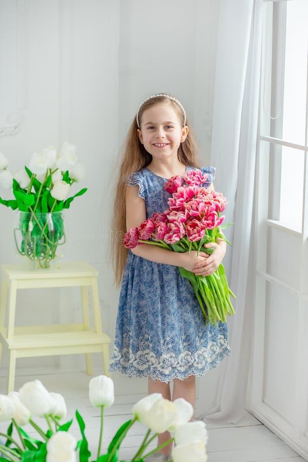 Retrato de una muchacha de ojos azules hermosa, niña entre las flores de la primavera en un cuarto brillante fotografía de archivo libre de regalías