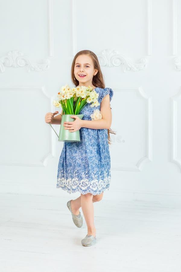 Retrato de una muchacha de ojos azules hermosa, niña entre las flores de la primavera en un cuarto brillante fotos de archivo libres de regalías